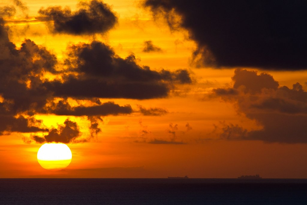sunset and cargo ships
